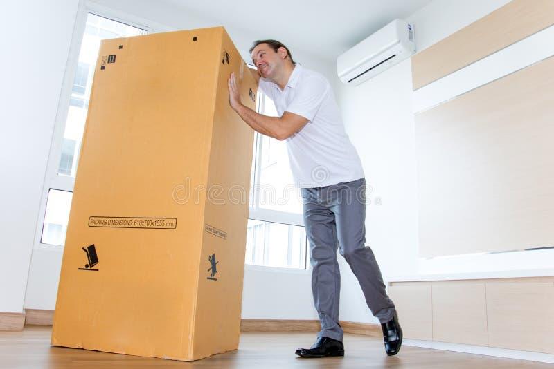 Um homem gosta de uma caixa de papel grande no apartamento imagem de stock royalty free