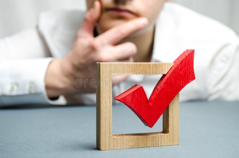 Um homem guarda sua mão no queixo e avalia o tiquetaque vermelho para um voto Avaliando a transparência da legalidade de uma elei imagens de stock