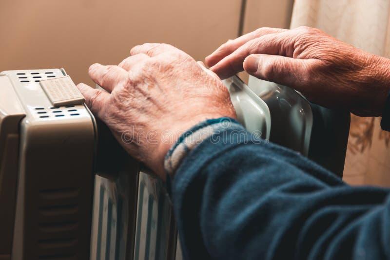 Um homem idoso aquece suas mãos sobre um calefator elétrico Na estação baixa, o aquecimento central é atrasado imagens de stock royalty free