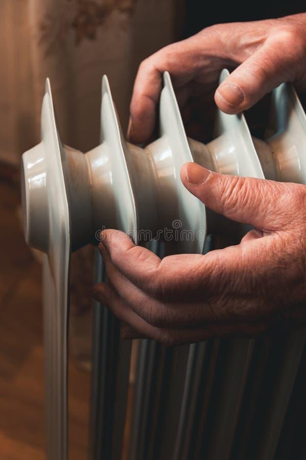 Um homem idoso aquece suas mãos sobre um calefator elétrico Na estação baixa, o aquecimento central é atrasado fotografia de stock