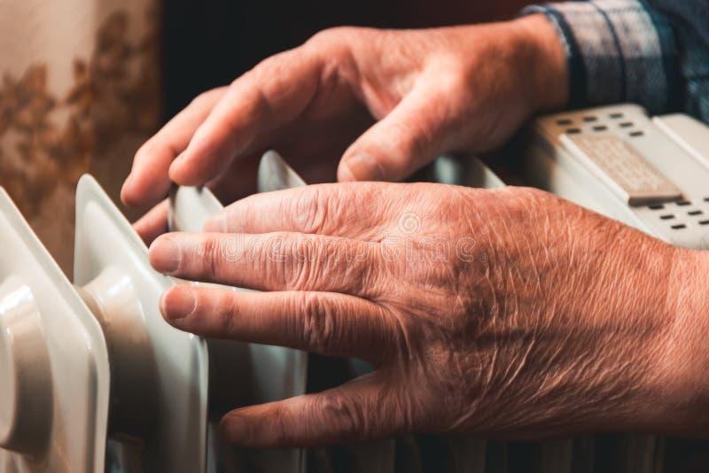 Um homem idoso aquece suas mãos sobre um calefator elétrico Na estação baixa, o aquecimento central é atrasado fotografia de stock royalty free