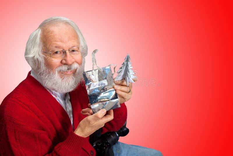 Um homem idoso com cabelo branco e barba em uma camiseta vermelha abre fotos de stock royalty free