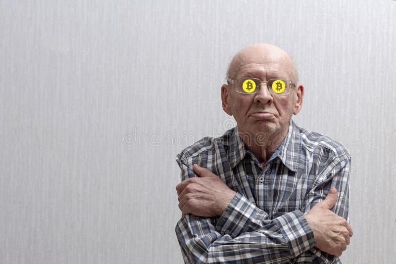 Um homem idoso com vidros em um fundo cinzento cruzou seus braços sobre sua caixa, e senta-se em seu sinal do bitcoin dos vidros foto de stock