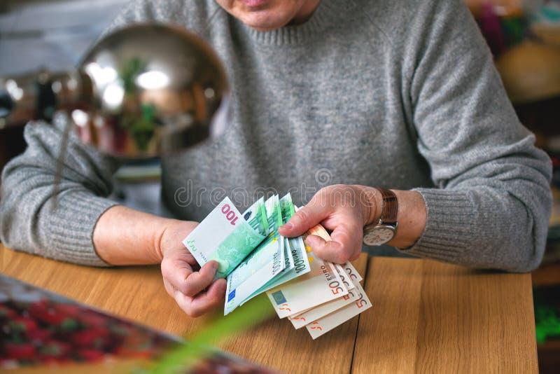 Um homem idoso conta o dinheiro, Euro imagens de stock