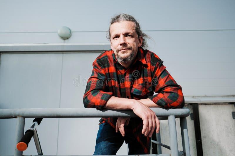 Um homem idoso do moderno com cabelo longo e uma barba em uma camisa de manta vermelha inclina-se nos trilhos contra uma construç fotografia de stock royalty free