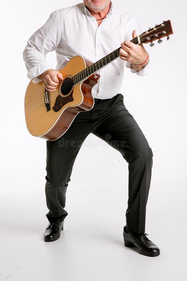 Um homem idoso está jogando uma guitarra isolada no fundo branco fotos de stock royalty free