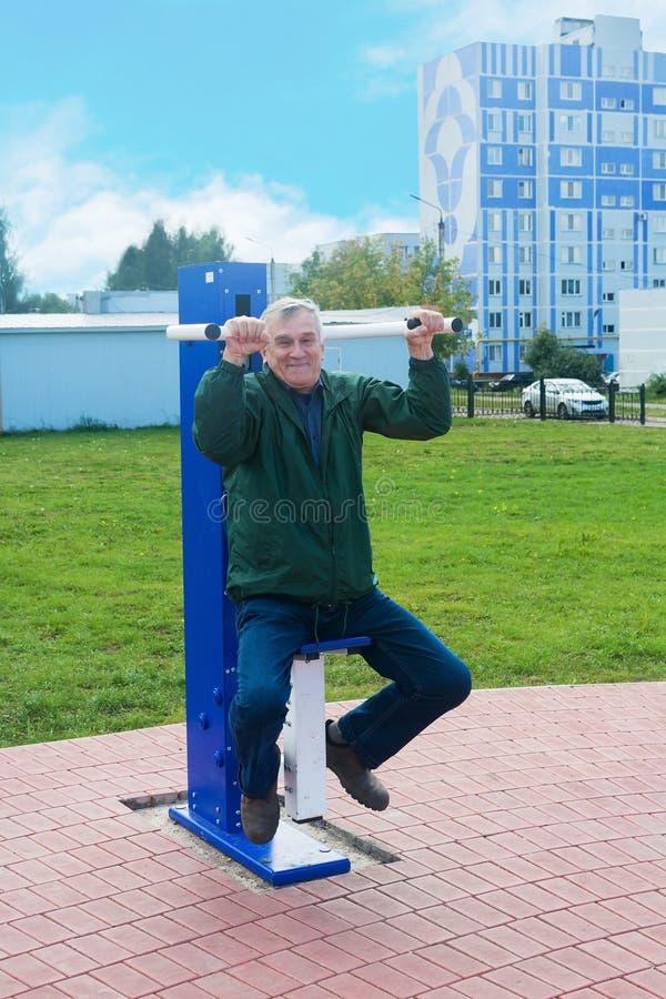 Um homem idoso está no gym na rua fotos de stock royalty free
