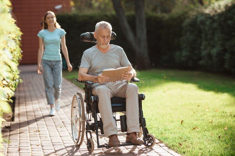 Um homem idoso está sentando-se em uma cadeira de rodas Atrás dele vem uma menina O ancião está lendo um livro fotografia de stock royalty free