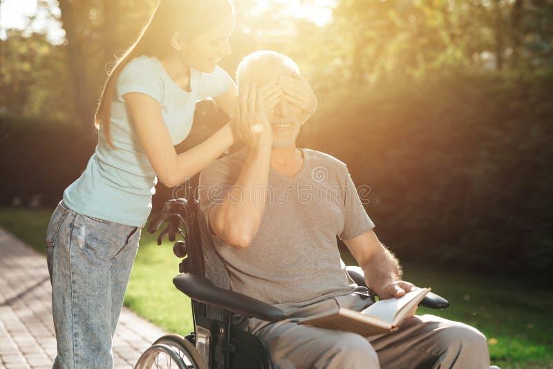 Um homem idoso está sentando-se em uma cadeira de rodas A menina está atrás dele e fecha seus olhos O ancião é livro de leitura foto de stock