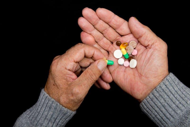 Um homem idoso guarda muitos comprimidos coloridos nas mãos velhas em um fundo escuro Idade avançada dolorosa Cuidados médicos de fotos de stock