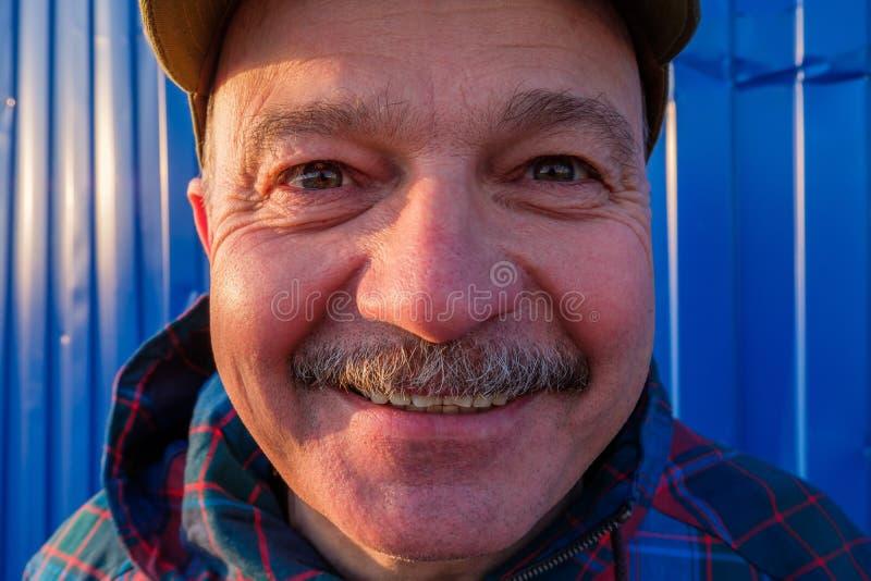 Um homem idoso no boné de beisebol olha e sorri no fundo fotos de stock royalty free