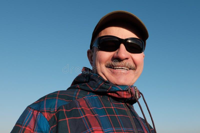Um homem idoso nos óculos de sol e em um boné de beisebol olha para baixo imagem de stock