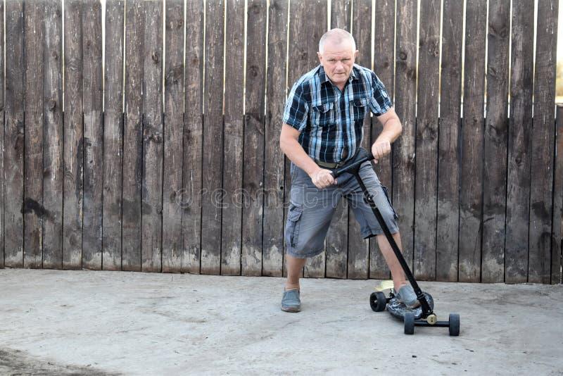 Um homem idoso tenta conduzir um 'trotinette' para ensinar seus filhos imagens de stock
