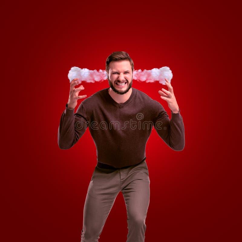 Um homem irritado no equipamento ocasional que inclina-se para a frente com o vapor que sai de suas orelhas no fundo vermelho fotos de stock royalty free