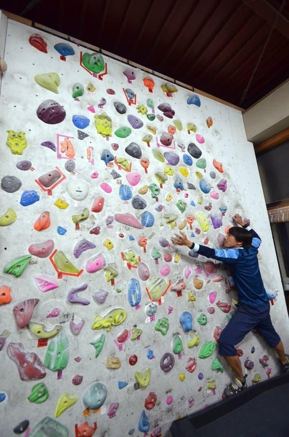 Um homem japonês que escala uma parede da rocha interna fotos de stock