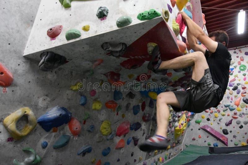 Um homem japonês que escala uma parede da rocha interna foto de stock