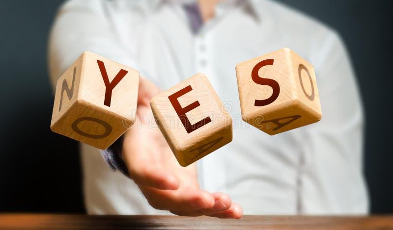 Um homem joga cubos com letras e inventa a palavra YES Acordo e aceitação, resposta à pergunta Coragem foto de stock