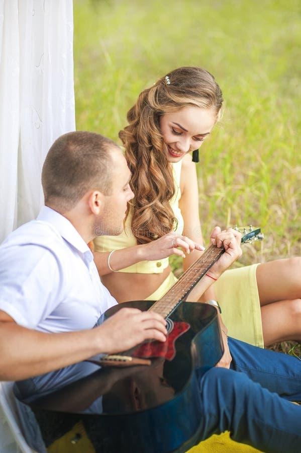 Um homem joga a guitarra amado Homem e mulher em uma cabana, o conceito do romance e idílio fotografia de stock royalty free