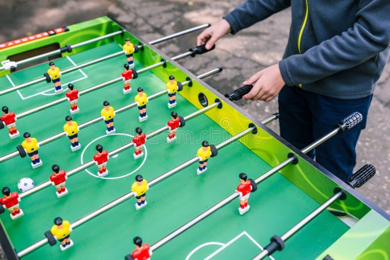 Um homem joga o futebol da tabela Jogo de mesa na rua Recrea??o e entretenimento no ver?o na rua para jovens fotografia de stock royalty free