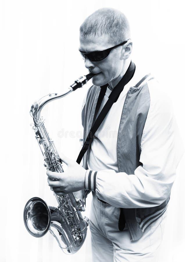 Um homem joga o saxofone foto de stock