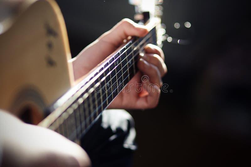Um homem joga uma música em uma guitarra acústica imagens de stock
