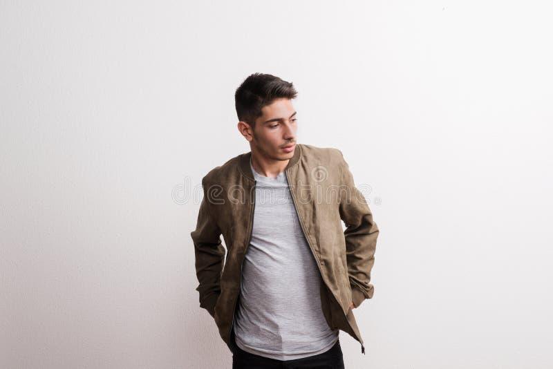 Um homem latino-americano novo seguro em um estúdio, mãos em uns bolsos imagem de stock