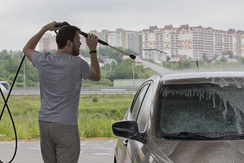 Um homem lava um carro em uma lavagem de carros, molhando o carro com mangueira de uma torneira Serviço da cidade para carros de  fotografia de stock