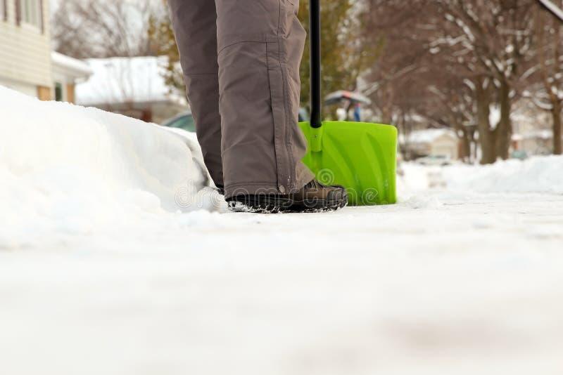 Um homem limpa a neve dos passeios com o snowblower imagem de stock