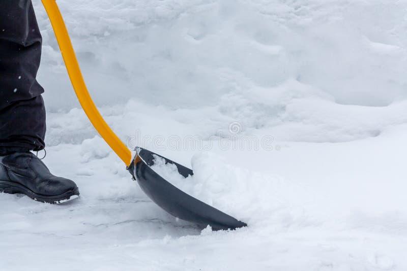 Um homem limpa a neve na jarda com uma pá após uma queda de neve pesada imagens de stock