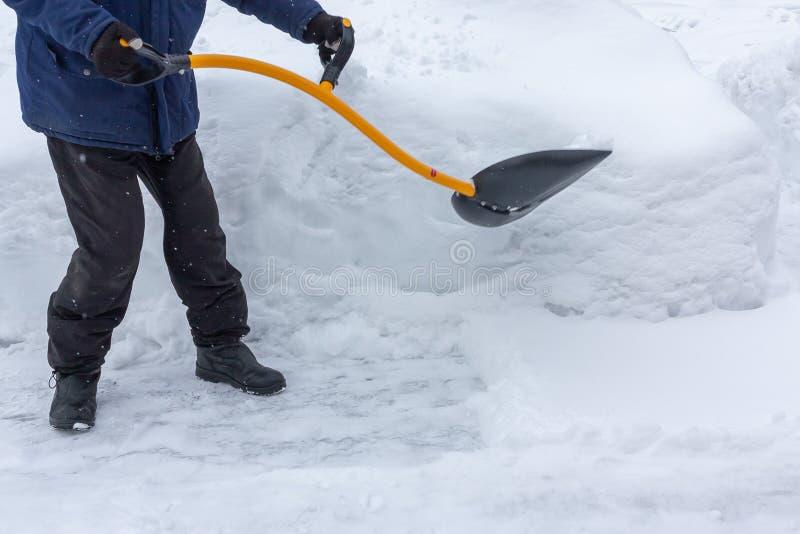 Um homem limpa a neve na jarda com uma pá após uma queda de neve pesada imagem de stock