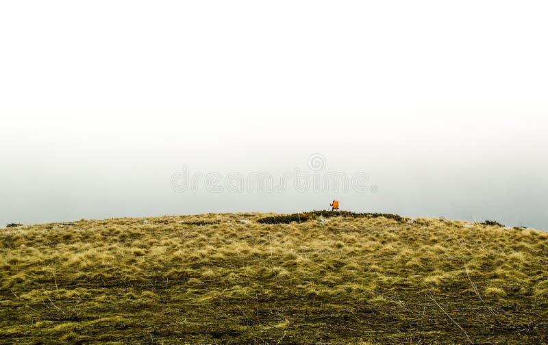 Um homem livre do lonelu na extremidade do mundo com a trouxa nas montanhas imagens de stock