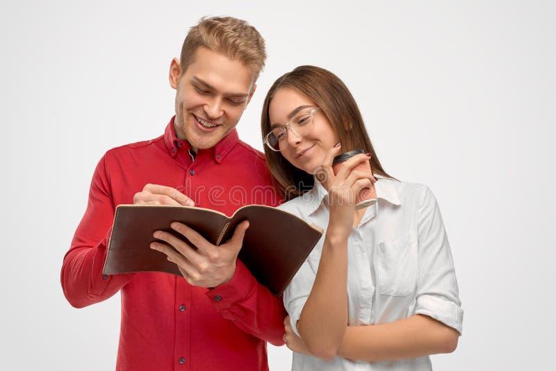 Um homem louro considerável com um sorriso neve-branco largo está feliz terminar a transação de negócio assinando o contrato imagens de stock