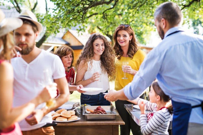 Um homem maduro com a família e os amigos que cozinham o alimento em um assado em um partido fora imagens de stock royalty free