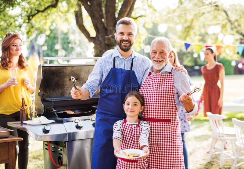 Um homem maduro com a família e os amigos que cozinham o alimento em um partido do assado foto de stock royalty free