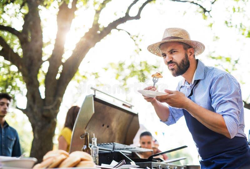 Um homem maduro com a família e os amigos que cozinham e que servem o alimento em um partido do assado imagem de stock