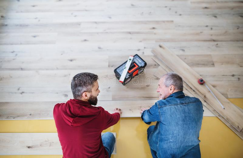 Um homem maduro com seu pai superior que coloca o revestimento de madeira, um conceito novo da casa fotos de stock royalty free