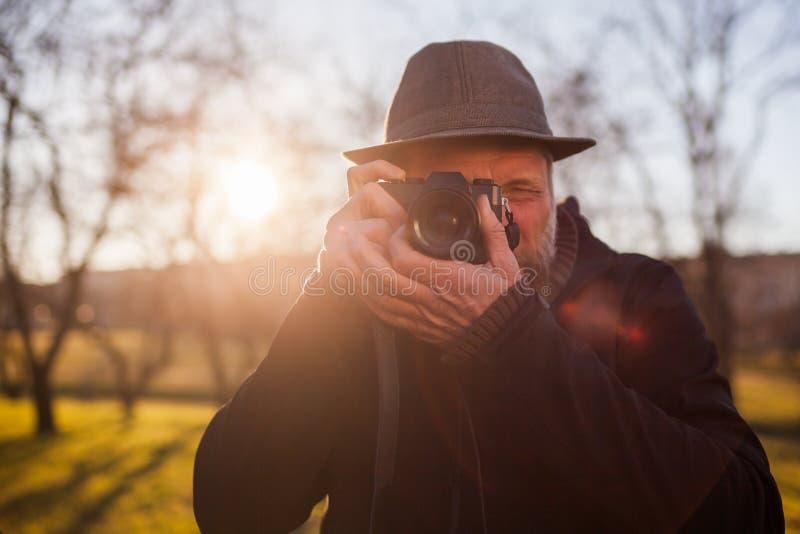Um homem maduro em um chapéu toma imagens em uma câmera mirrorless imagens de stock royalty free