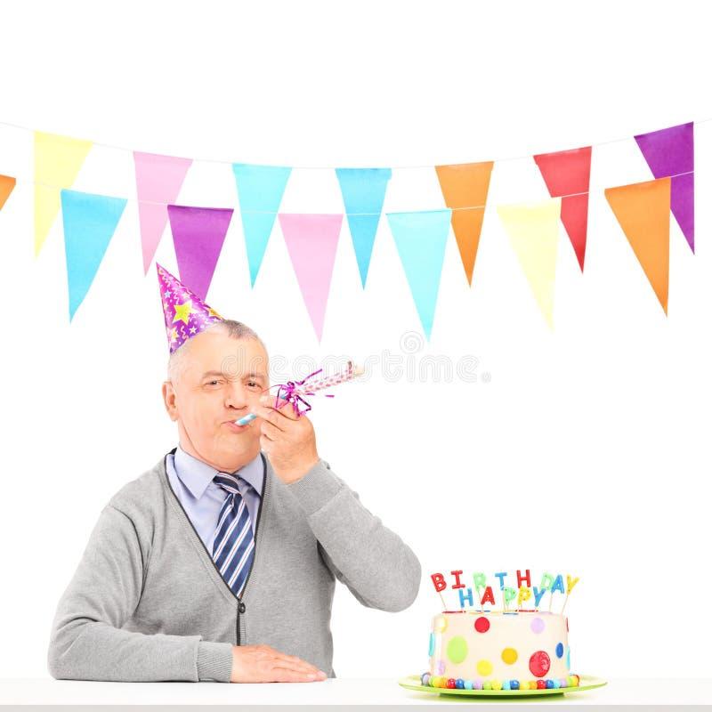 Um homem maduro feliz com sopro do chapéu do partido e um bolo de aniversário imagem de stock