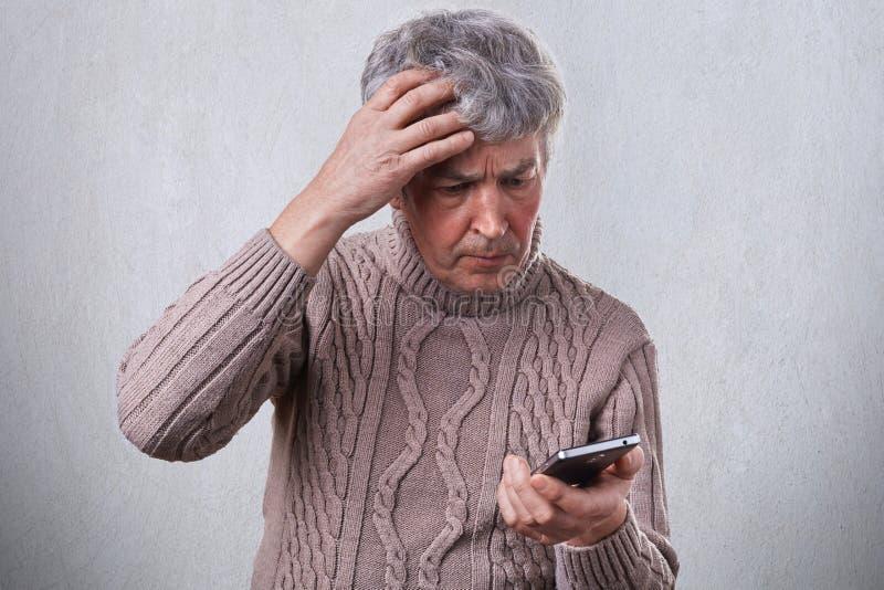 Um homem maduro incomodado que guarda sua mão em sua cabeça cinzenta ao usar o smartphone que lê alguma notícia no Internet Um ho foto de stock