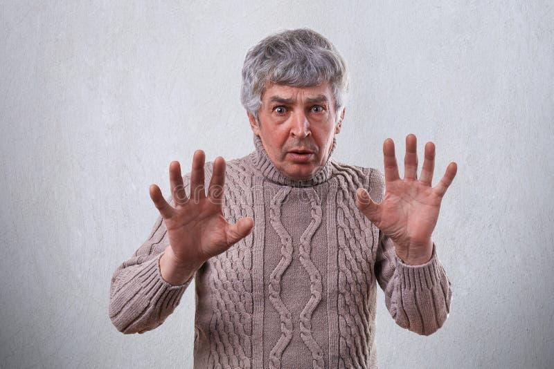 Um homem maduro irritado com expressão surpreendida e irritada que recusa algo ao não mostrar nenhum sinal com suas palmas Querer imagens de stock