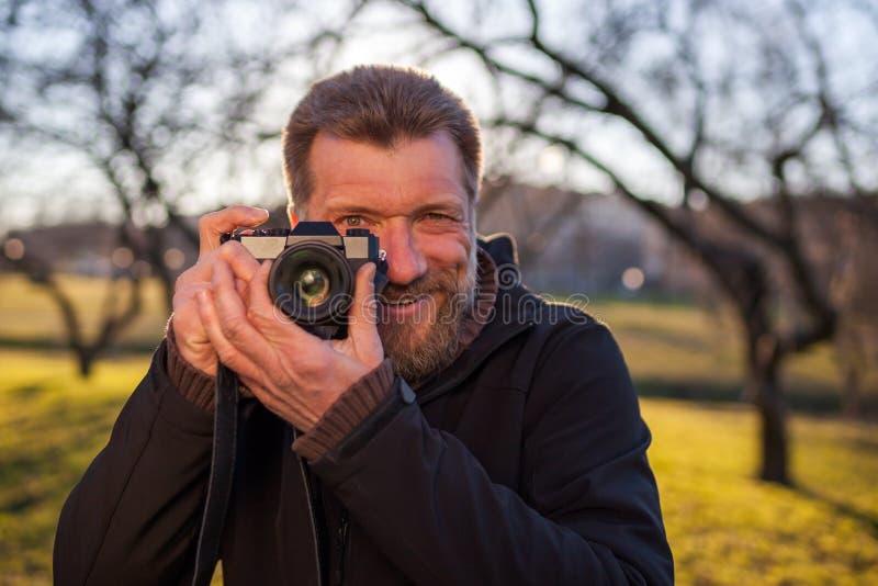 Um homem maduro toma imagens em uma câmera mirrorless fotografia de stock royalty free