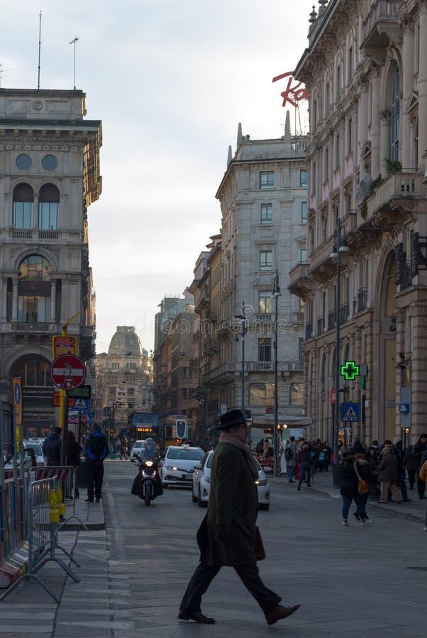 Um homem mais idoso que cruza a rua no centro de Milão, Itália fotografia de stock