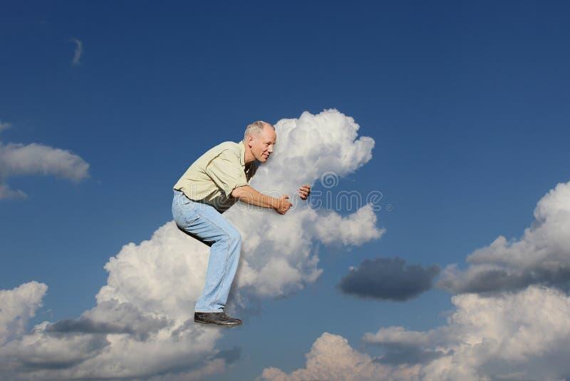 Um homem monta em uma nuvem na forma de um cão fotos de stock royalty free