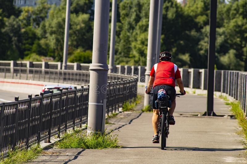 Um homem monta uma bicicleta Vista traseira Esportes e recrea??o fotos de stock royalty free