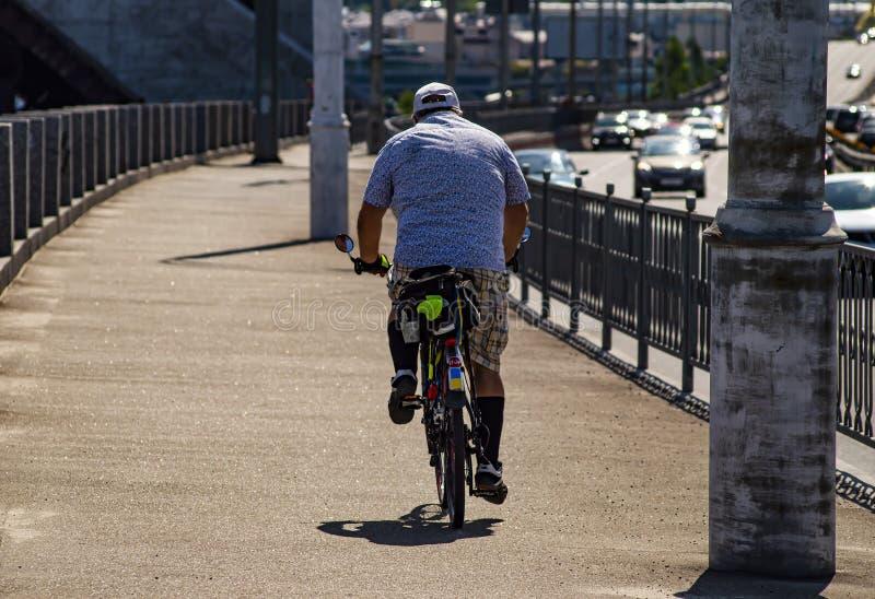 Um homem monta uma bicicleta Vista traseira Esportes e recrea??o fotos de stock