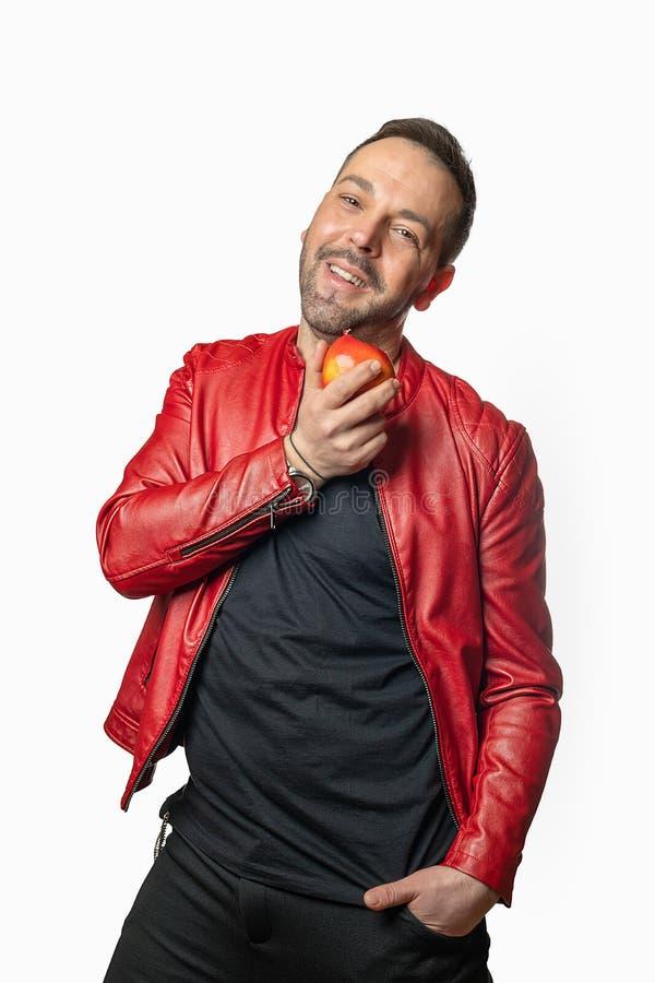 Um homem mostra um estilo de vida saudável com uma maçã em sua mão imagens de stock royalty free