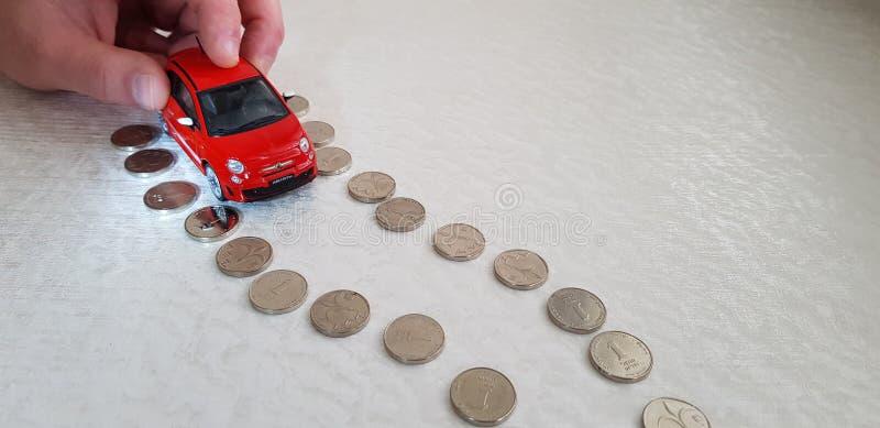 Um homem move-se com em seu brinquedo vermelho do abarth da autorização 500 dos dedos na linha da estrada feita de moedas israeli fotos de stock