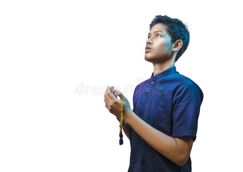 Um homem muçulmano asiático que veste um escuro - a camisa azul está rezando a Allah ao guardar grânulos de oração fotos de stock royalty free