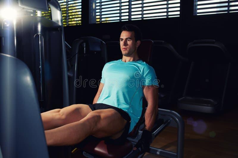 Um homem muscular novo da construção que exercita na máquina dos pés da imprensa no fitness center imagens de stock
