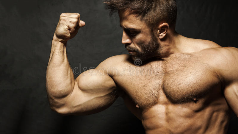 Um homem muscular que dobra seu bíceps foto de stock royalty free